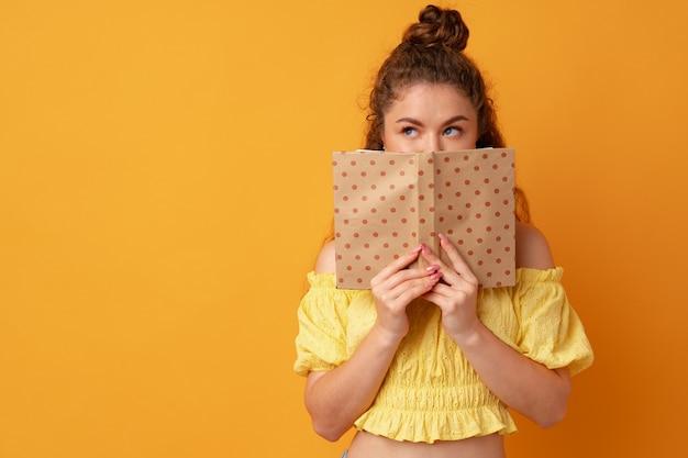Студент молодая фигурная женщина держит книгу на желтом фоне