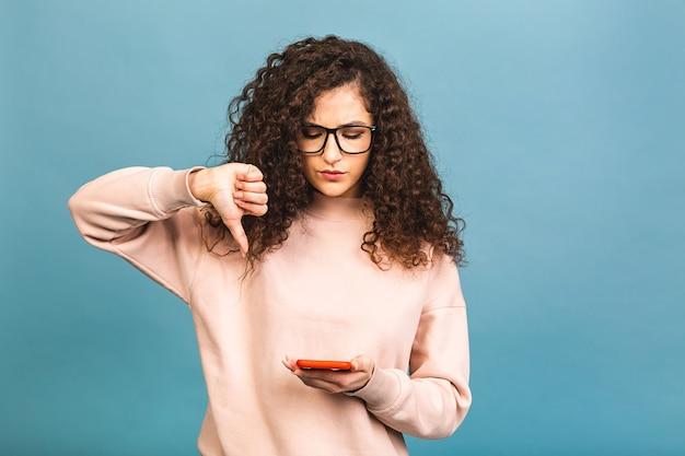 Молодая кудрявая женщина отправляет текстовое сообщение с помощью смартфона на изолированном синем фоне с сердитым лицом