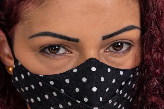 保護マスクを身に着けている若い巻き毛の女性