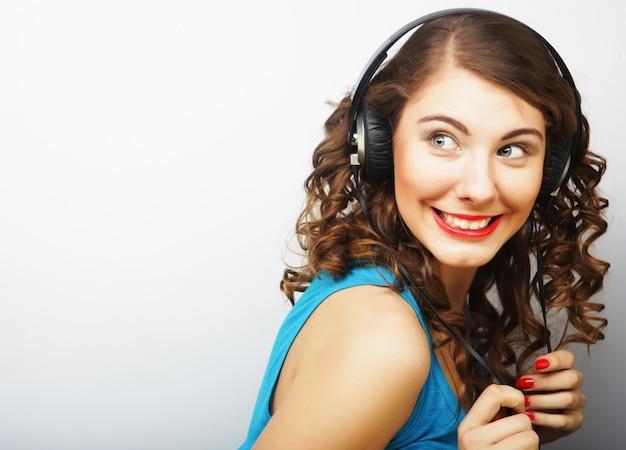 音楽を聴いているヘッドフォンを持つ若いカーリー女性。スタジオショット。