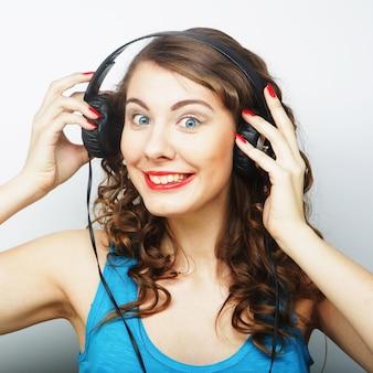 Молодая кудрявая женщина с наушниками, слушая музыку. студия выстрел.