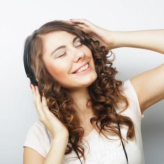 音楽を聴いているヘッドフォンを持つ若い巻き毛の女性。