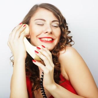 Молодая кудрявая женщина с винтажным телефоном.
