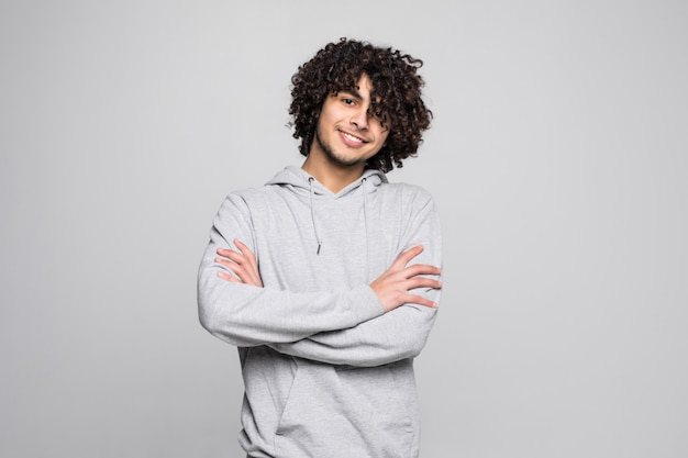 Young curly young man with crossed hands isolated on white wall