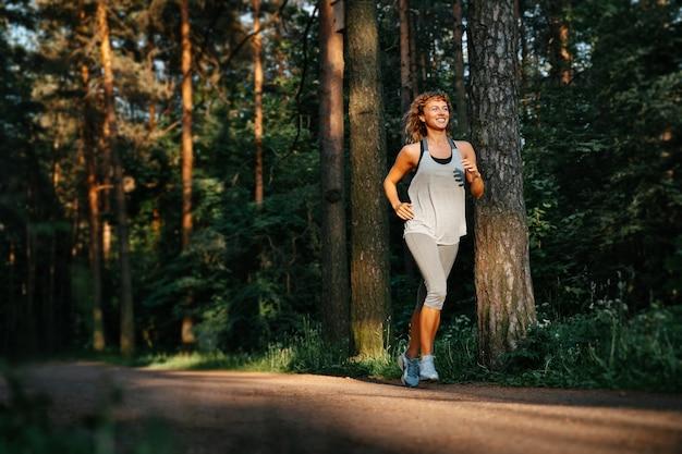 Молодая кудрявая женщина бежит по лесной дорожке парка и улыбается счастливой спортсменке, занимающейся фитнесом