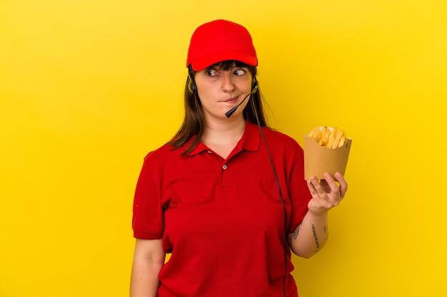 青い背景に分離されたフライドポテトを保持している若い曲線美の白人女性ファーストフードレストランの労働者は混乱し、疑わしく、不安を感じています。