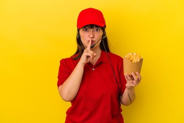 若い曲線美の白人女性ファーストフードレストランの労働者は、秘密を保持するか、沈黙を求めて青い背景で隔離のフライドポテトを保持しています。