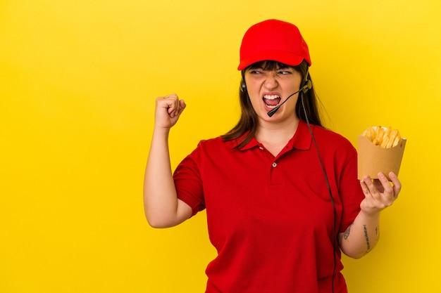 젊은 매력적인 백인 여성 패스트 푸드 레스토랑 직원은 승리, 승자 개념 후 주먹을 들고 파란색 배경에 고립 된 감자 튀김을 들고.