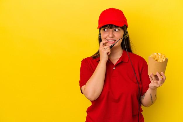 젊은 매력적인 백인 여성 패스트 푸드 레스토랑 직원은 파란색 배경에 고립 된 감자 튀김을 들고 복사 공간을 보고 뭔가에 대해 편안 하 게 생각.
