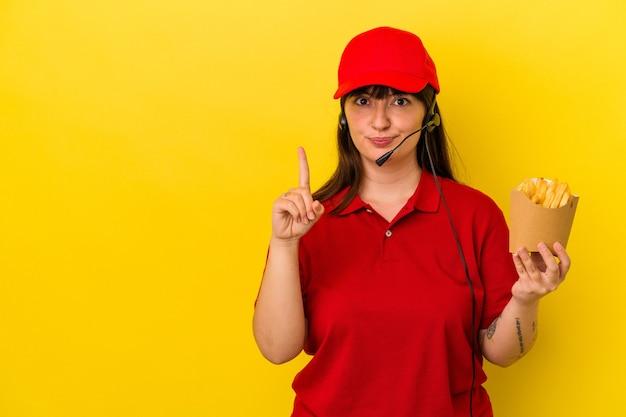 젊은 매력적인 백인 여성 패스트 푸드 레스토랑 직원 손가락으로 1 위를 보여주는 파란색 배경에 고립 된 감자 튀김을 들고.