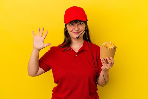 若い曲がりくねった白人女性ファーストフードレストランの労働者は、指で5番を示す陽気な笑顔の青い背景に分離されたフライドポテトを保持しています。