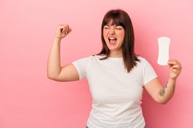 勝利、勝者の概念の後に拳を上げるピンクの背景に分離された湿布を保持している若い曲線美の白人女性。