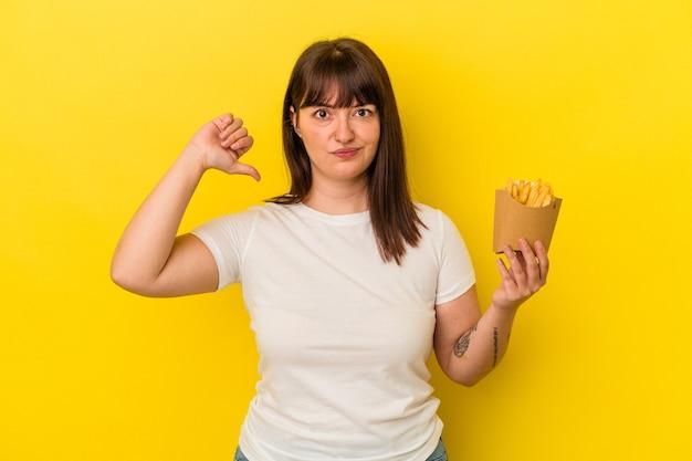 黄色の背景に分離されたフライドポテトを保持している若い曲線美の白人女性は、誇りと自信を感じています。