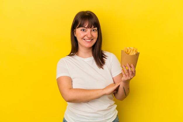 笑って楽しんで黄色の背景に分離されたフライドポテトを保持している若い曲がりくねった白人女性。