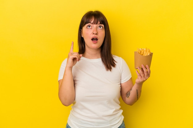 開いた口で逆さまを指している黄色の背景に分離されたフライドポテトを保持している若い曲がりくねった白人女性。