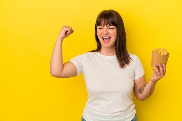 노란색 배경에 격리된 감자 튀김을 들고 있는 매력적인 백인 여성은 승리, 승자 개념으로 주먹을 쥔다.