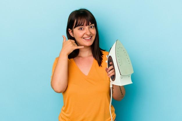Молодая пышная кавказская женщина, держащая утюг, изолирована на синем фоне, показывая жест мобильного телефона пальцами.