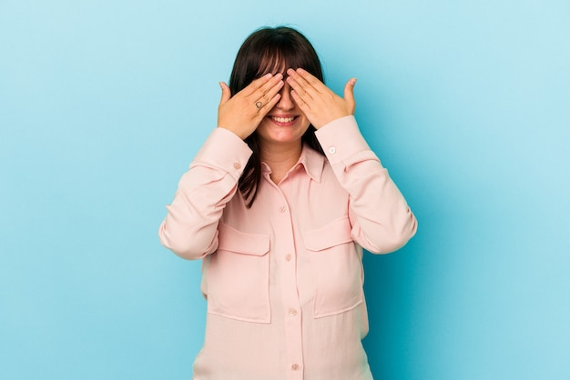 Young curvy caucasian woman isolated on blue background afraid covering eyes with hands.