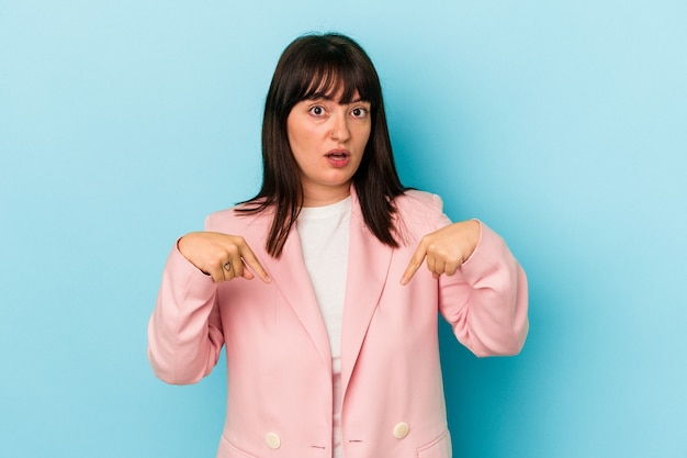 Young curvy caucasian woman isolated on blue background points down with fingers, positive feeling.