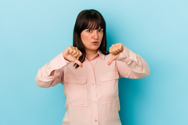 Young curvy caucasian woman isolated on blue background showing thumb down and expressing dislike.
