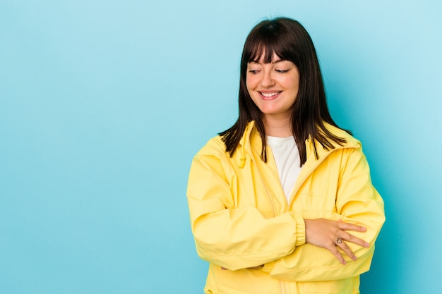 Young curvy caucasian woman isolated on blue background smiling confident with crossed arms.