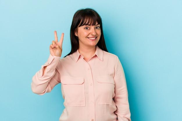 指で平和のシンボルを示す、楽しくてのんきな青い背景に分離された若い曲線美の白人女性。