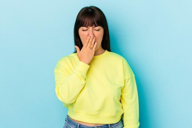 手で口を覆う疲れたジェスチャーを示すあくびをしている青い背景に分離された若い曲線美の白人女性。