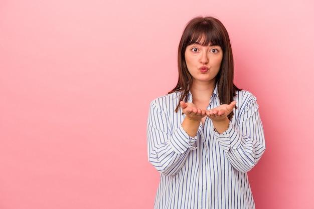 ピンクの背景に分離された若い曲線美の白人女性は、唇を折り、手のひらを持って空気のキスを送信します。
