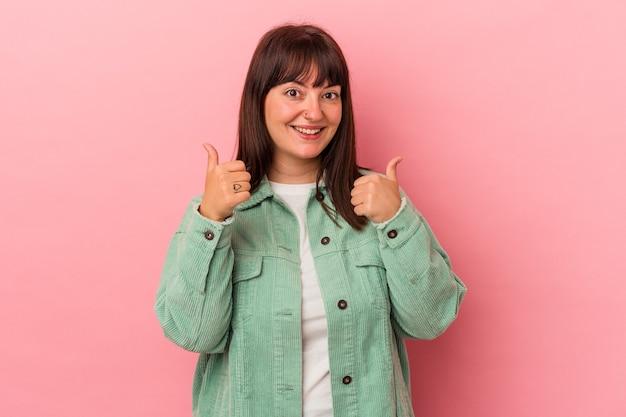 ピンクの背景に分離された若い曲線美の白人女性は、両方の親指を上げて、笑顔で自信を持っています。