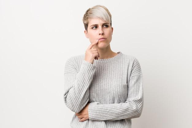 疑わしいと懐疑的な表情で横に見ている白で隔離される若い曲線の白人女性。