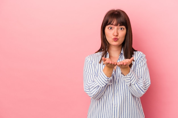 Young curvy caucasian woman isolated on pink background folding lips and holding palms to send air kiss.
