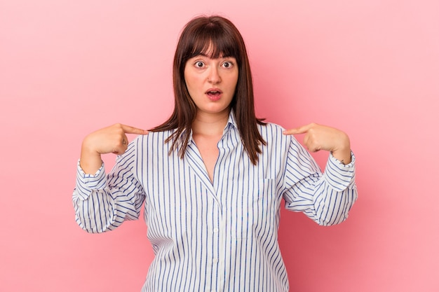 Young curvy caucasian woman isolated on pink background points down with fingers, positive feeling.