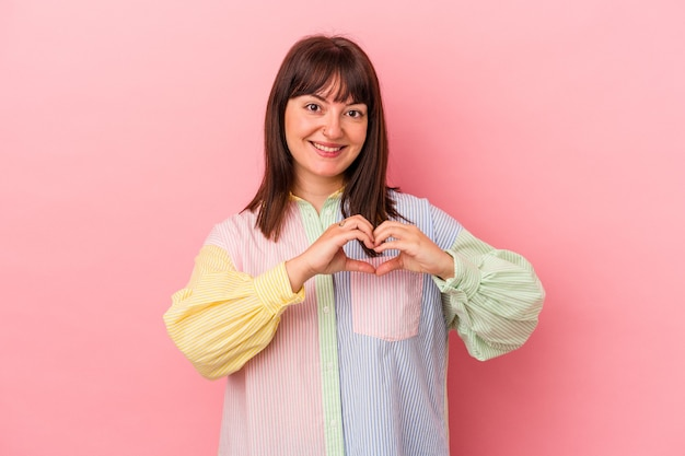 Young curvy caucasian woman isolated on pink background smiling and showing a heart shape with hands.