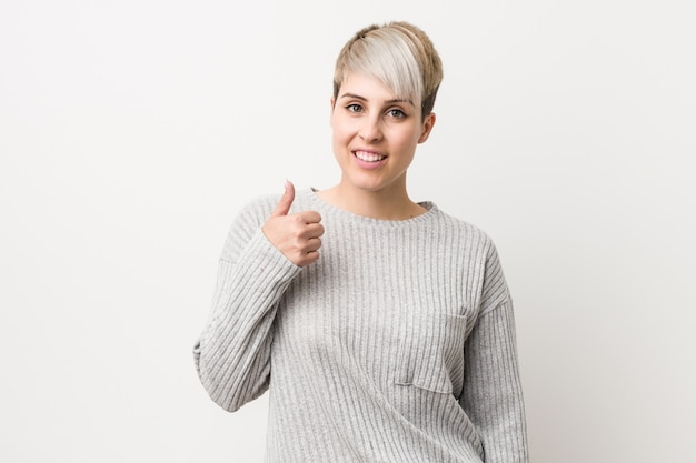 Young curvy caucasian woman isolated smiling and raising thumb up