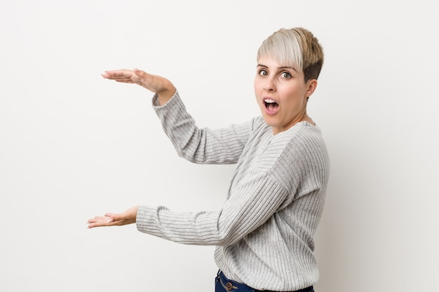 Young curvy caucasian woman isolated on white background shocked and amazed holding a copy space between hands.