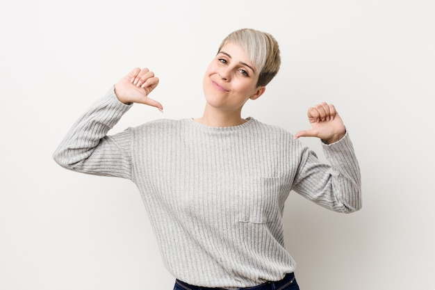 Young curvy caucasian woman isolated on white wall feels proud and self confident, example to follow.