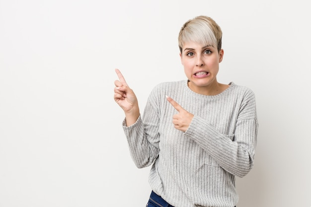 Young curvy caucasian woman isolated on white wall shocked pointing with index fingers to a copy space.