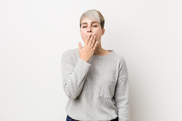 Young curvy caucasian woman isolated on white yawning showing a tired gesture covering mouth with hand.