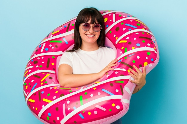 Young curvy caucasian woman with air mattress isolated on blue background laughing and having fun.