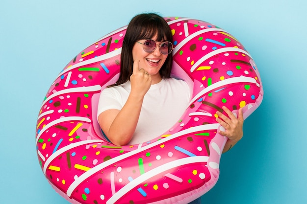 Young curvy caucasian woman with air mattress isolated on blue background pointing with finger at you as if inviting come closer.