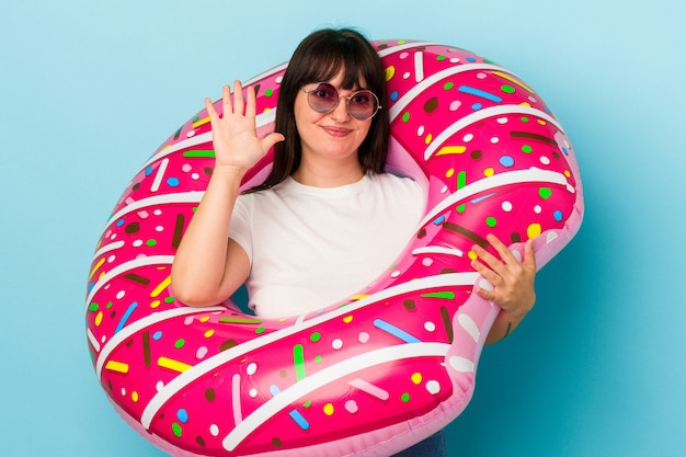 Young curvy caucasian woman with air mattress isolated on blue background smiling cheerful showing number five with fingers.