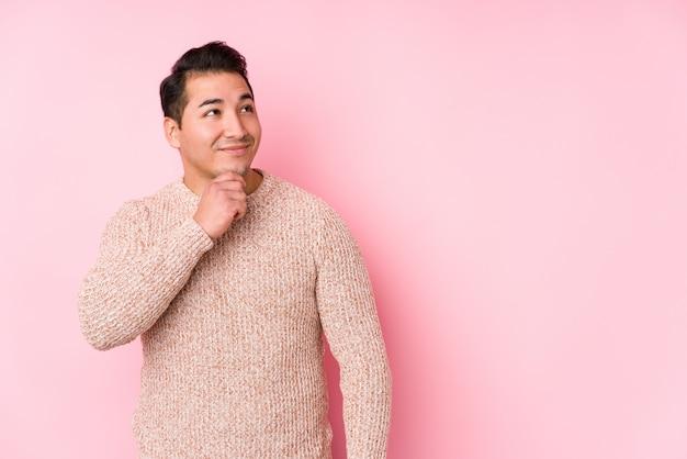 ピンクの壁でポーズをとって若い曲線の男は疑わしいと懐疑的な表情で横向きに分離しました。