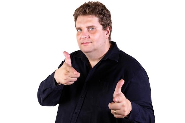 若い孤立した白い壁にポーズをとって曲がりくねった男は人差し指を指して興奮しています。