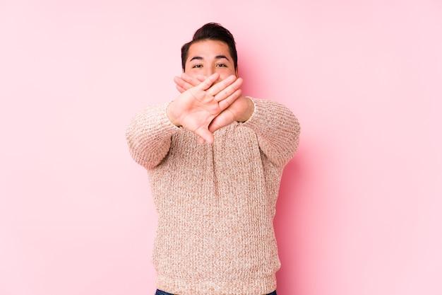 Молодой пышный мужчина позирует на розовом фоне изолированно, делая жест отрицания