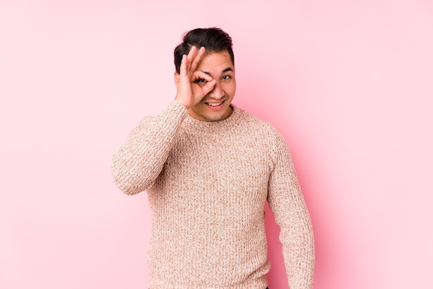 Young curvy man posing on pink background isolated excited keeping ok gesture on eye.