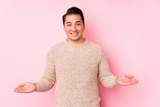 Young curvy man posing in a pink  isolated showing a welcome expression.