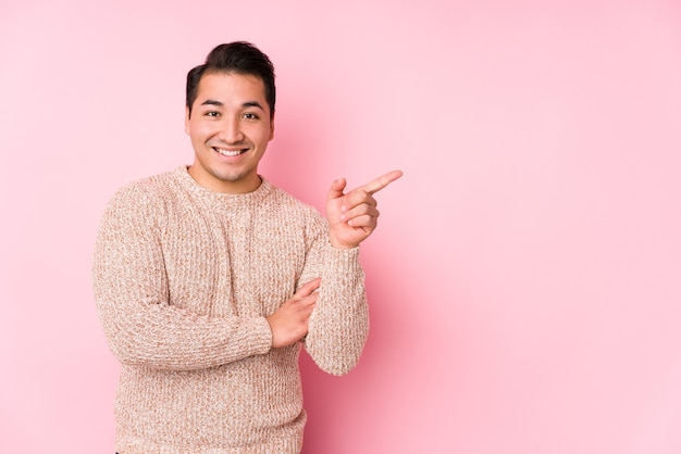 Young curvy man posing in a pink  isolated smiling cheerfully pointing with forefinger away.