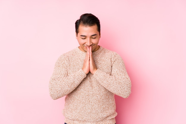 Young curvy man posing in a pink wall isolated holding hands in pray near mouth, feels confident.