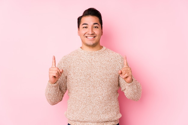 Young curvy man posing in a pink wall isolated indicates with both fore fingers up showing a blank space.