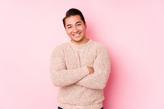 Young curvy man posing in a pink wall isolated laughing and having fun.